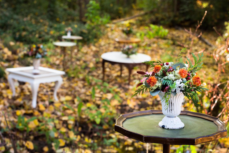 diferentes mesitas auxiliares con detalle floral y decoracion en un bosque