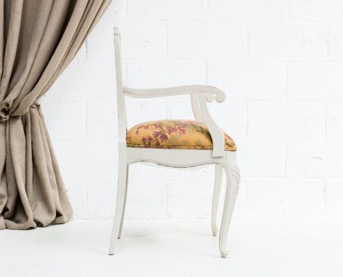 silla de madera gris envejecida con reposabrazos y asiento estampado de flores en beige verdes y rosas