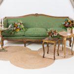 rincon con sofa vintage color verde y mesitas auxiliares color dorado con flores y alfombras