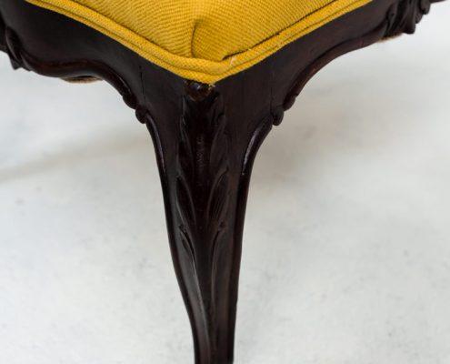 silla baja descalzadora vintage de madera oscura y tapizada en color mostaza