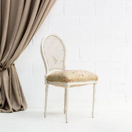 Decoración romántica de bodas en Madrid con silla vintage estilo romántico de madera y rejilla color blanco y tela de flores.