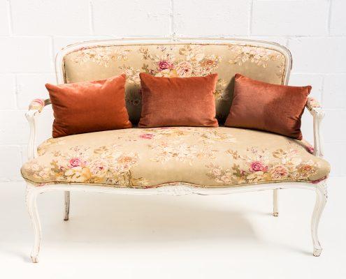 sofa antiguo estilo romantico de madera color blanco decapado y tapizado en tela estampada color beige y rosa palo
