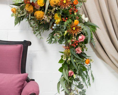 rincon con sofa de dos plazas estilo romantico tapizado en tela color malva con una mesa baja y detalles flor