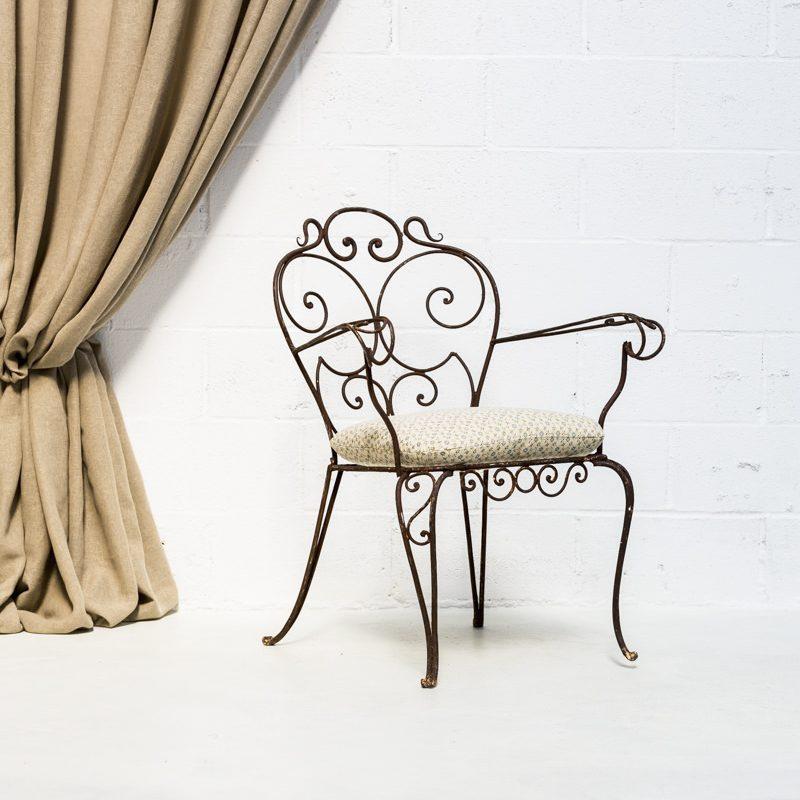 Mobiliario romántico en Madrid, silla de forja estilo afrancesado en color marrón y cojín.